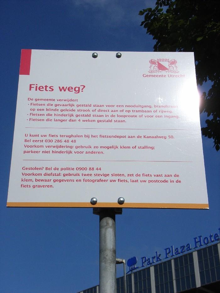 Foto van bord naast de geleidelijn met de tekst: de gemeente verwijdert fietsen die gevaarlijk gestald staan op een geleidelijn