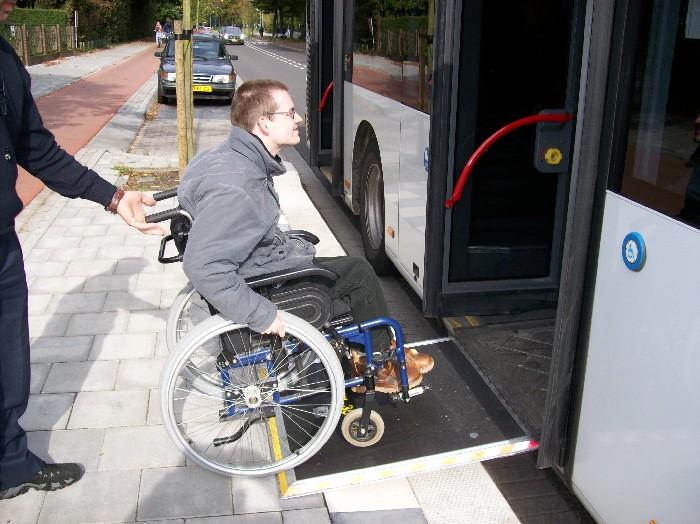 Foto van rolstoeler die de bus in rijdt.